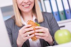 Vrouw op het kantoor die lunch hebben Concept voor healty of ongezond voedsel op het werk royalty-vrije stock afbeeldingen