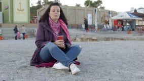 Vrouw op het openbare strand, drinkt zij thee Tegen de achtergrond van vele mensen Zijaanzicht Ruwe verwerkte 4k stock videobeelden