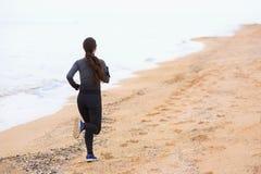 Vrouw op het strand in werking dat wordt gesteld dat stock fotografie
