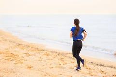 Vrouw op het strand in werking dat wordt gesteld dat stock afbeelding