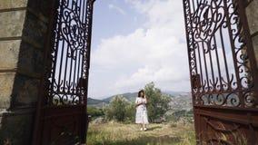 Vrouw op ingangspoorten van de villa van Portugal tussen heuvels stock videobeelden