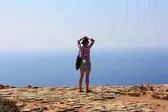 Vrouw op klip door overzees in Cyprus Stock Afbeeldingen