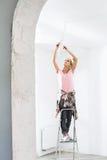 Vrouw op ladder die gloeilamp in nieuw huis passen stock afbeeldingen