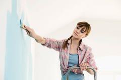 Vrouw op ladder het schilderen muur met penseel stock foto