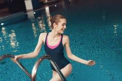Vrouw op ladder van de pool bij de gymnastiek Zij kijkt gelukkig, modieus en paste in één stuk stock afbeelding