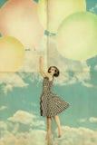 Vrouw op luchtballen in blauwe hemel met wolken royalty-vrije stock afbeelding