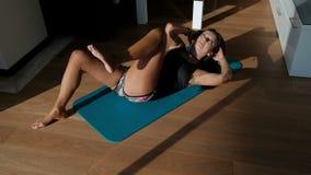 Vrouw op mat die lichaams het buigen en draai doen terwijl het liggen op de vloer stock footage