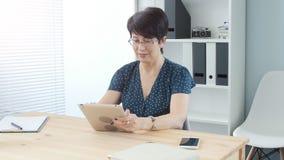 Vrouw op middelbare leeftijd in bureau die aan digitale tablet werken stock footage