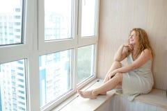 Vrouw op middelbare leeftijd dichtbij venster Royalty-vrije Stock Foto's
