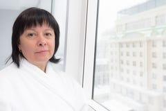 Vrouw op middelbare leeftijd door het venster royalty-vrije stock foto