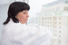 Vrouw op middelbare leeftijd door het venster stock foto's
