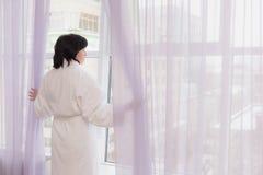 Vrouw op middelbare leeftijd door het venster stock afbeeldingen