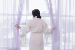 Vrouw op middelbare leeftijd door het venster royalty-vrije stock foto's