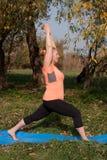 Vrouw op middelbare leeftijd in een oranje yoga van de T-shirtpraktijk in aard royalty-vrije stock fotografie