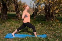 Vrouw op middelbare leeftijd in een oranje yoga van de T-shirtpraktijk in aard stock fotografie