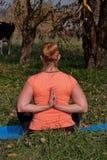 Vrouw op middelbare leeftijd in een oranje yoga van de T-shirtpraktijk in aard royalty-vrije stock foto