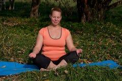 Vrouw op middelbare leeftijd in een oranje yoga van de T-shirtpraktijk in aard stock afbeeldingen