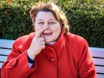 Vrouw op middelbare leeftijd in een rode laag die in het Park rusten royalty-vrije stock afbeelding