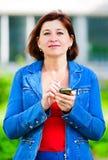Vrouw op middelbare leeftijd met cellphone stock foto's
