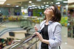 Vrouw op middelbare leeftijd met een kop van koffie, het centrum van het achtergrondwinkelcomplexvermaak stock foto's