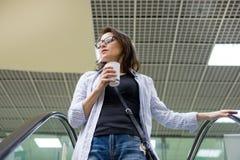 Vrouw op middelbare leeftijd met een kop van koffie, het centrum van het achtergrondwinkelcomplexvermaak stock afbeelding