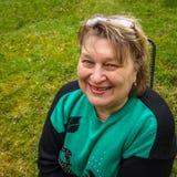 Vrouw op middelbare leeftijd met glazen die in het Park rusten stock afbeelding