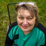 Vrouw op middelbare leeftijd met glazen die in het Park rusten royalty-vrije stock afbeelding