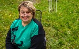 Vrouw op middelbare leeftijd met glazen die in het Park rusten royalty-vrije stock foto's
