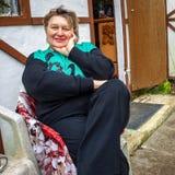 Vrouw op middelbare leeftijd met glazen die in het Park rusten stock fotografie