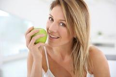 Vrouw op middelbare leeftijd met groene appel Royalty-vrije Stock Foto's