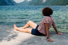Vrouw op middelbare leeftijd met krullende haarzitting door het meer royalty-vrije stock foto