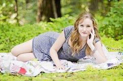 Vrouw op picknickdeken stock afbeeldingen