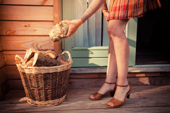 Vrouw op portiek die logboeken voor brandhout krijgen royalty-vrije stock fotografie