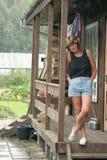 Vrouw op portiek van huis in het land Stock Fotografie