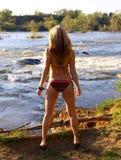 Vrouw op rivierbank Stock Foto's