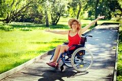 Vrouw op rolstoel het toenemen handen omhoog Stock Afbeeldingen