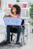 Vrouw op rolstoel sorterende wasserij royalty-vrije stock foto