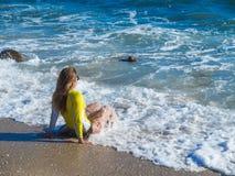 Vrouw op rotsachtig strand Royalty-vrije Stock Afbeeldingen
