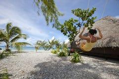 Vrouw op schommelingsvoorzijde van blauwe lagune Royalty-vrije Stock Foto's