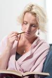 Vrouw op Sofa Bites Pencil While Concentrating op Boek wordt gezeten dat royalty-vrije stock foto's