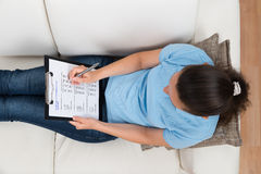 Vrouw op Sofa Filling Survey Form Royalty-vrije Stock Fotografie