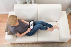 Vrouw op Sofa Shopping Online With Digital-Tablet stock fotografie