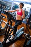Vrouw op stepper in gymnastiek Stock Foto's