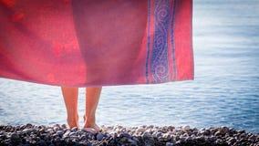 Vrouw op strand die heupen behandelen met handdoek royalty-vrije stock afbeelding