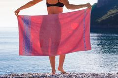 Vrouw op strand die heupen behandelen met handdoek royalty-vrije stock afbeeldingen