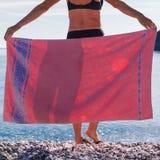 Vrouw op strand die heupen behandelen met handdoek stock foto's