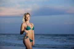 Vrouw op strand in groene bikini stock afbeeldingen