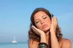 Vrouw op strand met muziek op hoofdtelefoons Stock Afbeeldingen