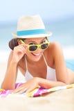 Vrouw op strand met zonnebril Stock Foto's