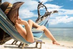 Vrouw op strandvakantie in hangmat door overzees Stock Fotografie